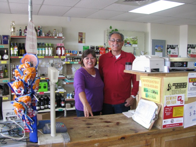 Above, standing behind on of their Grocery Store's cash registers, are Isabel and Roberto Gutierrez.