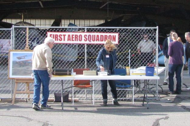 Braving the stiff breeze are Bill Madden at left, and Dr. Martin on the right, busily setting up the FASF Information Table.