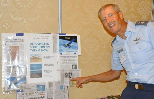 Colonel Fisher enthusiastically pointing to some current news clippings about the ongoing Convention.