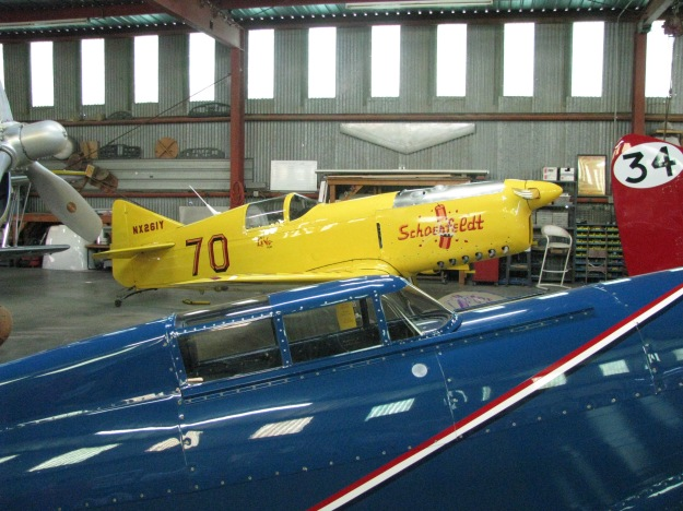 "Above, in the Flabob Racing hangar,  in its original bright yellow paint, is the famed Schoenfeldt ""Firecracker"" race plane piloted by renown test pilot Tony Levier, back in 1938, when he used it to win the International Air Races at Oakland, CA.  Of special note is that the USAF's one time First Aero Squadron Commander, Major General Patrick Halloran, flew this same replica airship many years later after WWII.  General Halloran is also well known for having been one of the few SR-71 Blackbird and early U-2 pilots during his tour as commanding officer of the First Aero Squadron."