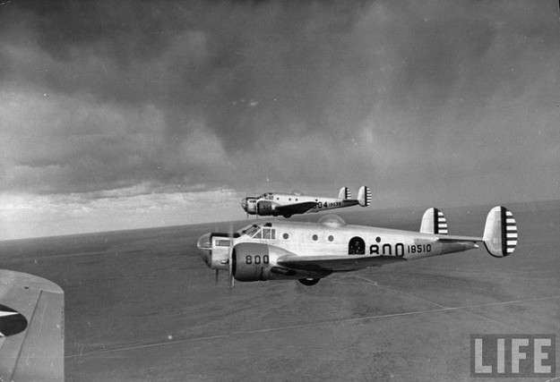 "Pair of Beech AT-11 ""Kansan"" bombardier training craft in flight over New Mexico desert during WWII"