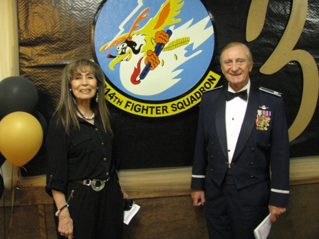 Julie Pitt and Colonel Pitt pose before the 314th Fighter Squadron's Logo.