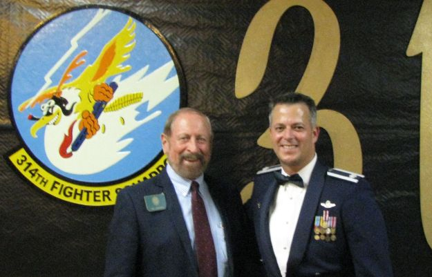 Daedalian Ric Lambart and 324th CO, Lt. Colonel Finch Caggiano stand before the 314th's emblem.