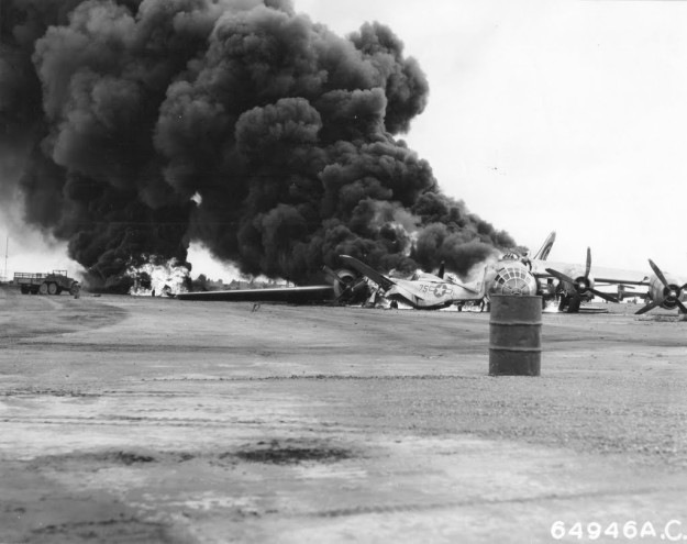 "A Boeing B-29 Superfortress and North American P-51 ""Mustangs"" burn furiously on a runway at Iwo Jima, Bonin Islands. The B-29, which was returning from a bombing mission on 24. April 1945, developed engine trouble over the island, and, while attempting to make an emergency landing, crashed into nine P-51s parked on the runway. Four of the Mustangs were destroyed and five were damaged. The bomber was from the 39th Bomb Squadron, 504th Bomb Group, 313th Bomb Wing, based on Tinian, Marianas Islands."