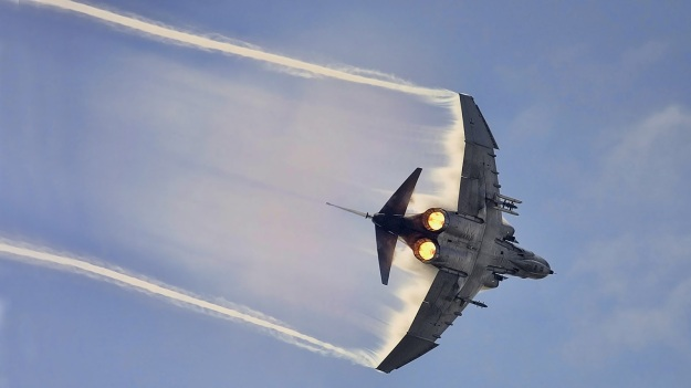 Phantom in tight turn in moist air, which creates cloud-like effects from the compression waves
