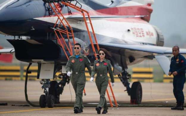 Captain Yu and her Co-Pilot stride from their J-10 Fighter.