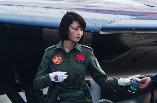 Captain Yu Xu of the PLA Air Force standing by her front-line Figher, the J-10