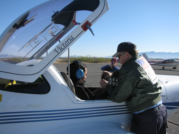 Colonel Orton explains flight plan and cockpit layout to next student.